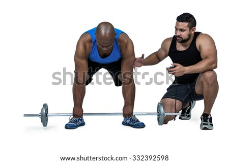 Man lifting barbell with trainer on white background - stock photo