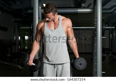 Man Lifting Dumbbell In Gym. Young Athlete In Gym Exercising With Dumbbell - stock photo