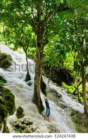 Man lifting his hands at waterfall, Chiang Mai, North of Thailand. - stock photo