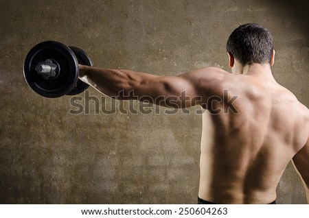 Man lifting weights, back image at old gym.