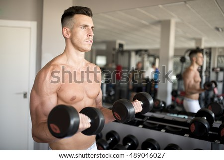 Man lifting weights training biceps in gym