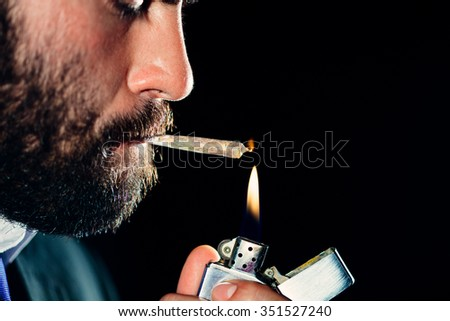 Man lighting and smoking a joint - stock photo