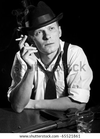 Man like a chicago gangster rests with submachine gun - stock photo