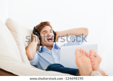 Man listening music in headphone excited sing song on the sofa with laptop at home, young handsome guy happy smile relax listen to music - stock photo