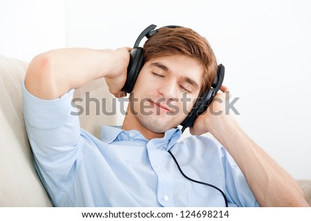 Man listening music in headphone on the sofa at home, young handsome guy happy smile relax listen to music with closed eyes