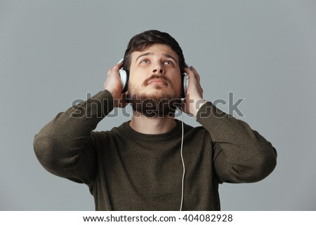 Man listening music in headphones over gray background