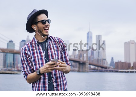 Man listening music with his smartphone in Brooklyn, New York - stock photo