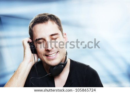 man listening the music in front of abstract background - stock photo