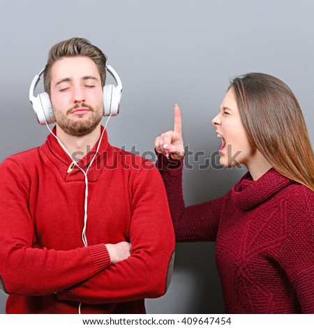 Man listening to music and doesnt care about her screaming at him - stock photo