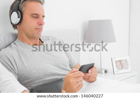 Man listening to music on his smartphone at home in bed