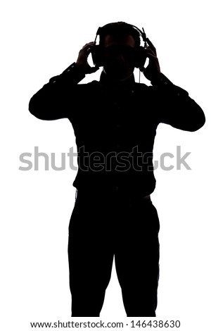 Man listening to music with headphones in silhouette isolated over white background  - stock photo