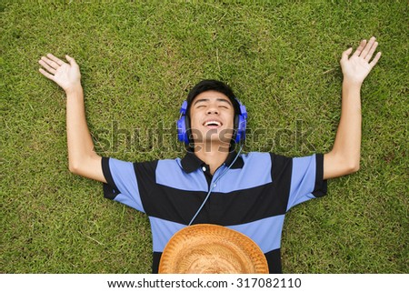 Man listening to music with headphones on grass outdoors - stock photo