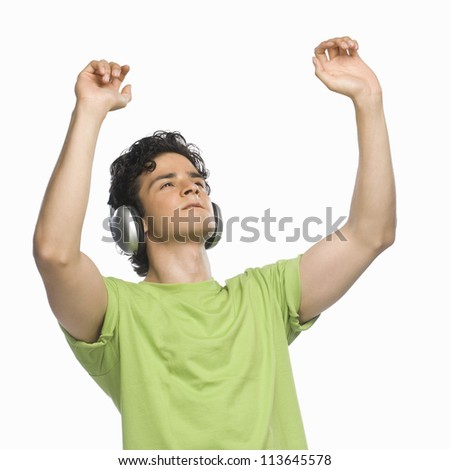 Man listening to music with his hands raised