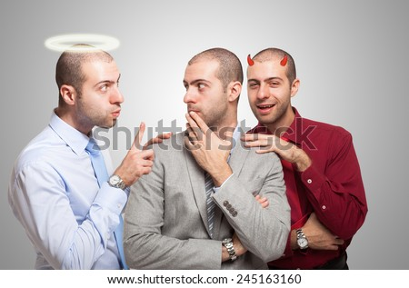 Man listening to the angel and devil self to make a choice - stock photo