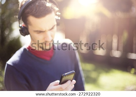 Man listening to the music from smartphone with wireless bluetooth technology. Focus on smartphone - stock photo