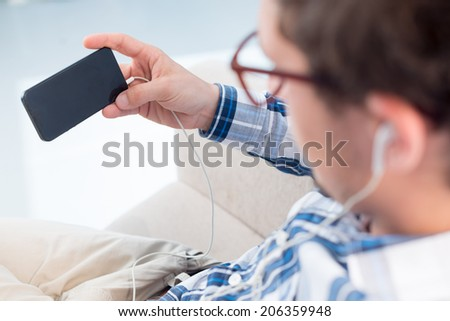 Man listening to the musing and holding smartphone - stock photo