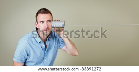Man listening to tin can telephone - stock photo