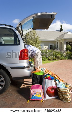 Man loading boot of car with luggage, side view - stock photo