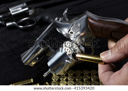Man loading compact magnum revolver firearm Closeup - stock photo