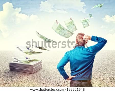 man look his money fly away - stock photo
