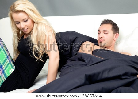 Man looking appreciatively at his beautiful blond girlfriend or wife as she prepares to get out of the bed that they are sharing