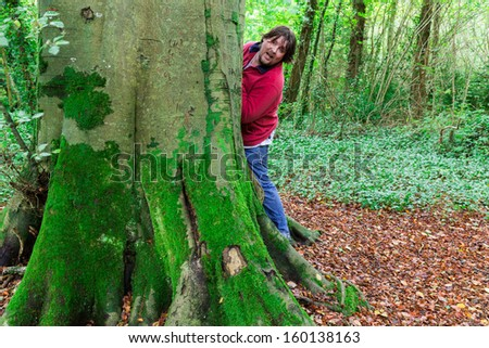 Man looking around a tree paying hide and seek in a forest