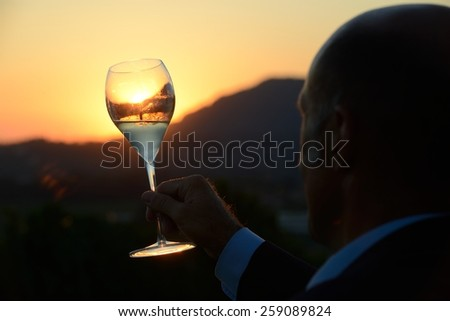 man looking at a glass of wine at sunset