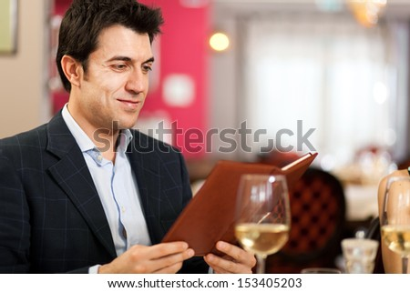 Man looking at a menu in the restaurant