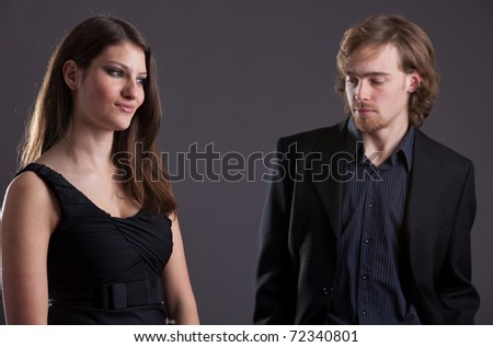 Man looking at a pretty woman who appears not to be interested - stock photo