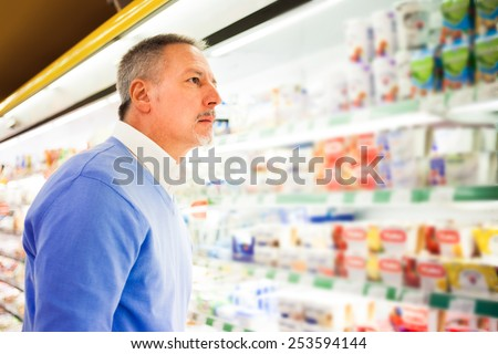 Man looking at a product in a supermarket - stock photo