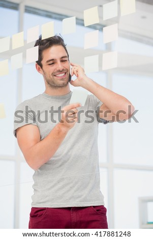 Man looking at a sticky notes while talking on phone at office