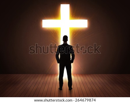 Man looking at bright cross sign concept - stock photo