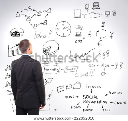 man looking at business strategy on the wall - stock photo