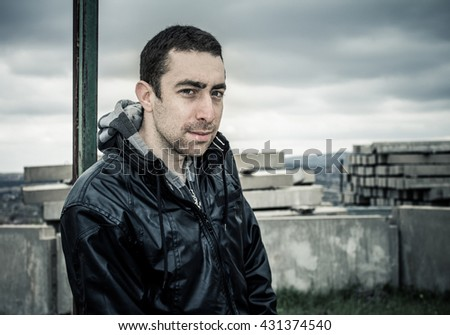Man looking at camera with sly smile on his serious face. - stock photo