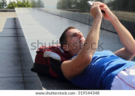Man looking at cell, mobile phone after workout. Running, jogging, sport, active lifestyle concept. Male athlete resting and relaxing after workout. - stock photo