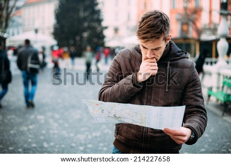 Man looking at city map on a trip. Looking for directions. - stock photo