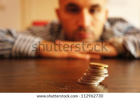 Man looking at coins and thinks - stock photo