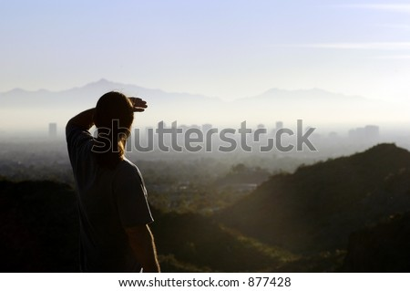 man looking at distant city - stock photo