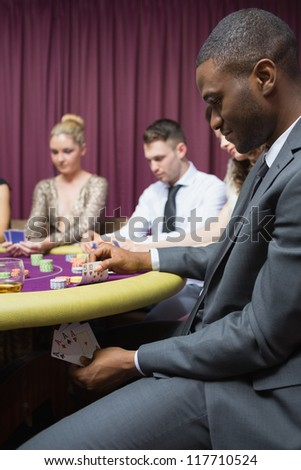 Man looking at four of a kind hand under table in casino - stock photo