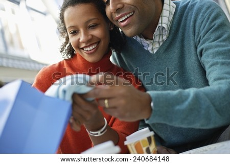 Man Looking at Girlfriend's Purchase - stock photo