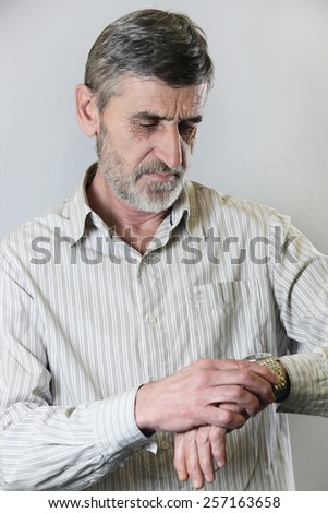 Man looking at his watch, A portrait of a middle aged man looking at the time on his wrist watch - stock photo