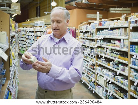 Man Looking at Homeopathic Medicines in Health Food Store - stock photo