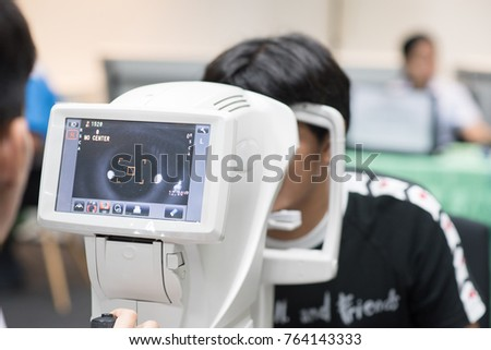 Man looking at refractometer eye test machine in ophthalmology