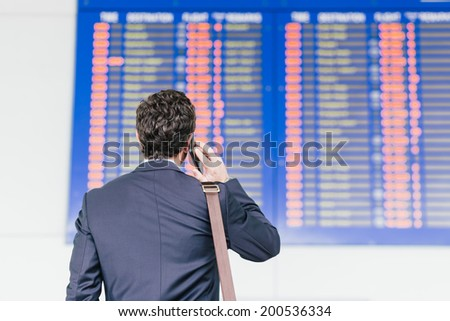 Man looking at the airline schedule and talking on the phone, rear view - stock photo