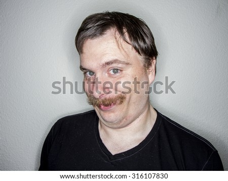 Man looking at the camera at an angle with a huge smile - stock photo