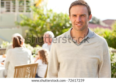 Man looking at the camera in the garden - stock photo