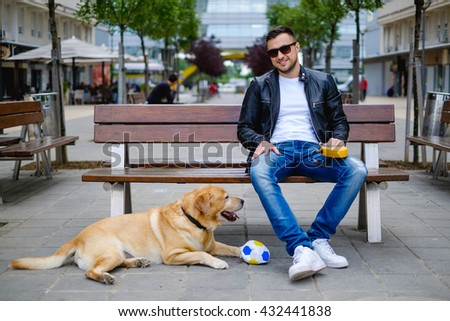 Man looking at the camera with his dog, Labrador lying beside him - stock photo