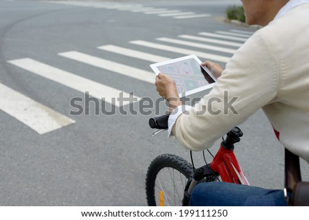 Man looking at the city map in his digital tablet, rear view - stock photo