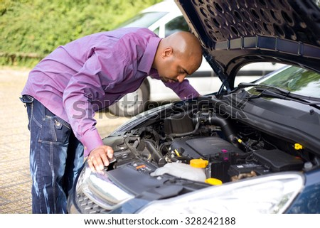 man looking at the engine of his car - stock photo