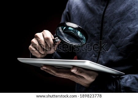 Man looking at the screen of a digital tablet with a magnifier - stock photo